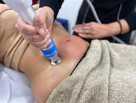 Una mujer recibiendo nuestro tratamiento de ondas de choque en Tenerife. Realizado en nuestro centro estético.